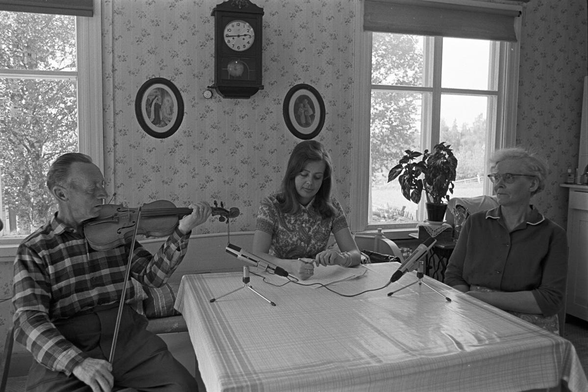 Man med fiol och stråke sitter vid matbord mittemot sin hustru, mellan dem ung Ann-Mari. På bordet står mikrofoner.