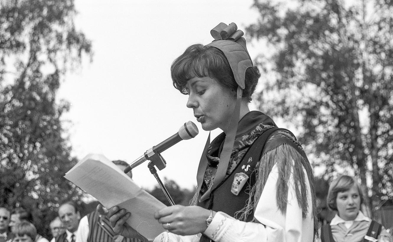 Ann-Mari Häggman håller tal i folkdräkt.