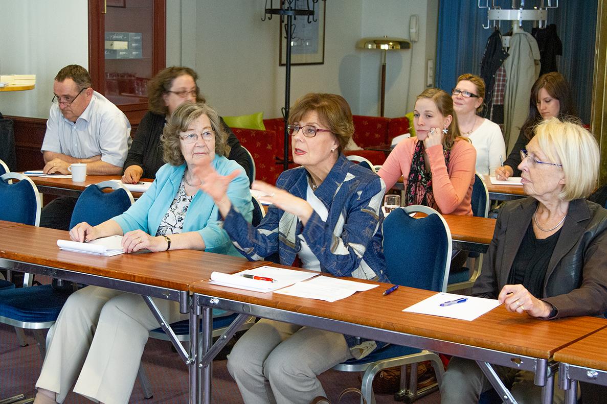 Ann-Mari Häggman talar, de andra i främsta raden lyssnar vända mot henne.