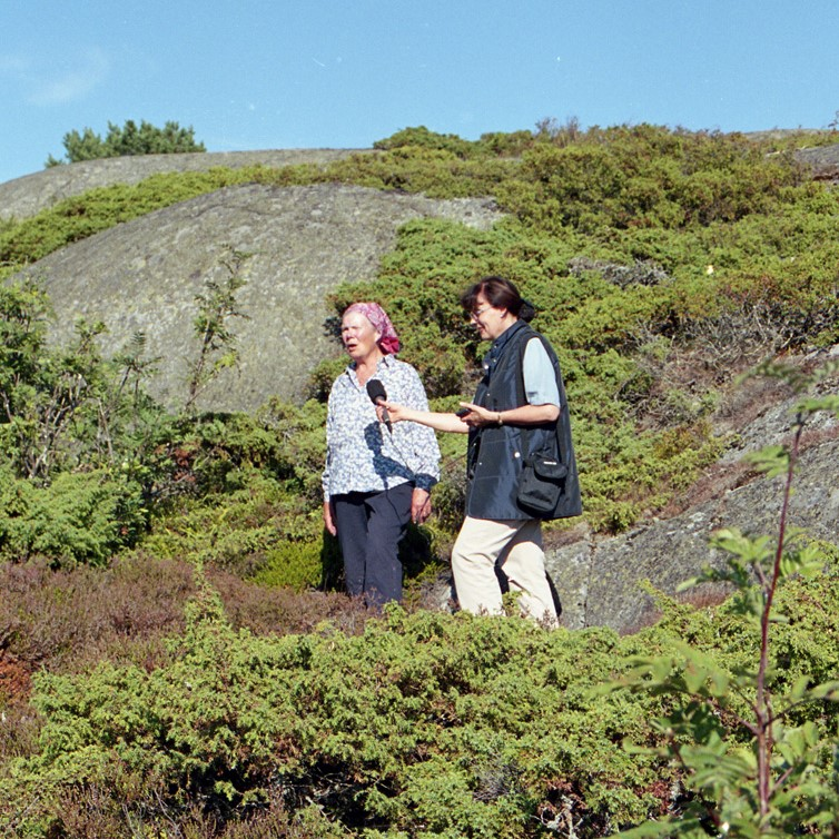 Kvinnorna står i en klippig sluttning i soligt väder.