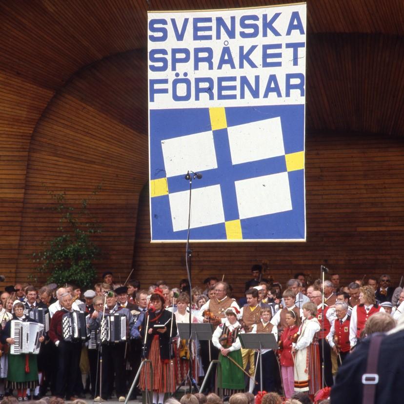Många spelmän och kvinnor står tätt bredvid varandra på scen, ovanför scenen plakat med texten Svenska språket förenar.